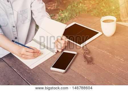 Woman Hand Writing Notebook And Phone, Tablet On Table In Garden At Coffee Shop With Vintage Toned.