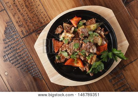 Fried lamb meat slices with vegetables in a pan. Wooden background.