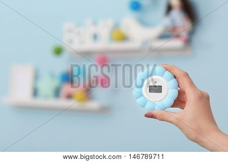 Woman checking temperature and humidity in baby room