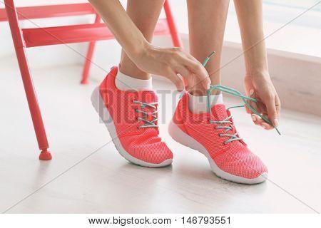 Woman tying her pink sneakers