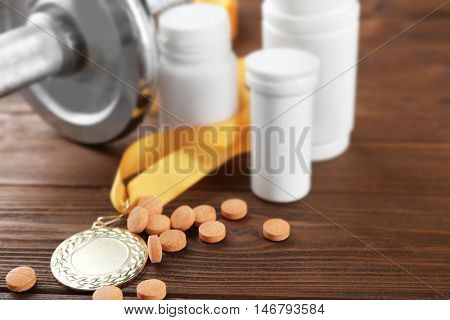 Dope in sports. Dumbbell, medal and drugs on wooden background