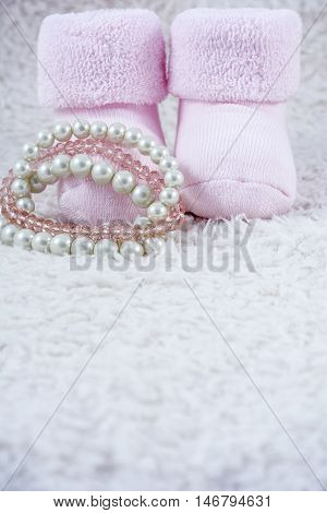 Pink booties for babies with several bracelets on the white fur
