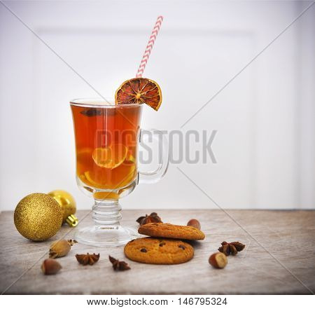 Hot winter tea with spices - cinnamon cloves and star anise and cookies with nuts on a light wooden background