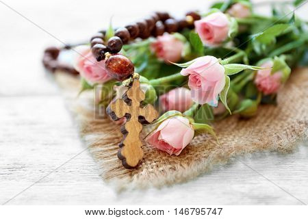 Wooden cross with flowers on sackcloth, closeup