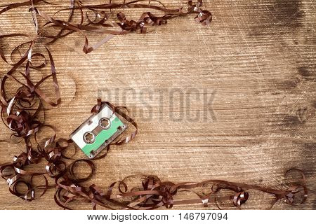 Audio cassette with pulled out tape on wooden background. Copy-space.