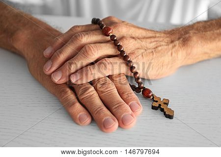 Wrinkled hands with wooden rosary