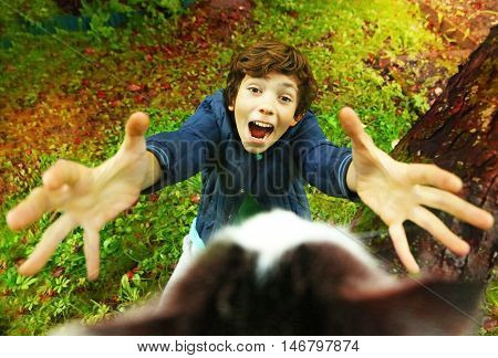 preteen handsome boy try to take the cat off the tree on the autumn garden background