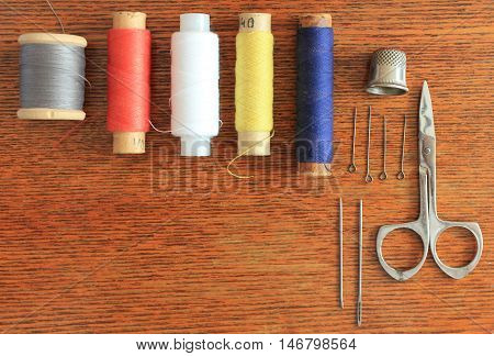 Sewing tools and accessories isolated on wooden table textured background spools of threads different colors, thimble, pins, needles, scissors top view close up