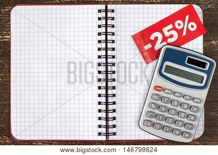 Digital calculator and blank notebook with tag of discount or sale