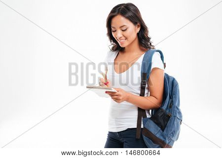 Cheerful attractive asian girl with backpack making notes in notebook isolated on a white background