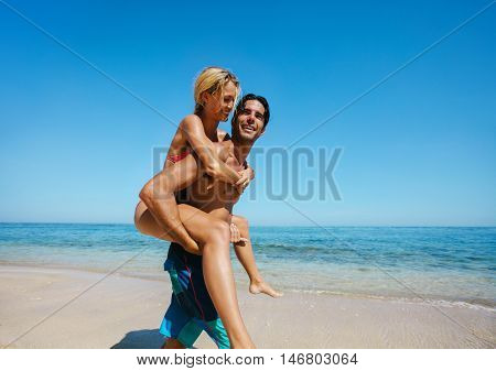 Side view shot of young man caring his girlfriend on back at the beach. Couple enjoying piggybacking on the sea shore.