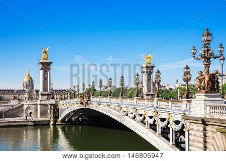 Pont Alexandre III bridge over river Seine and Hotel des Invalides in the background in the summer morning. Bridge decorated with ornate Art Nouveau lamps and sculptures. Paris France