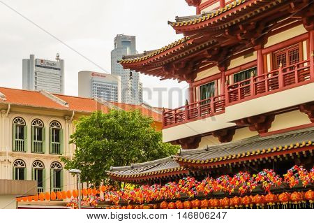 SINGAPORE, REPUBLIC OF SINGAPORE - JANUARY 09, 2014: Buddha Toothe Relic Temple and Singapore business district as background. Chinatown, Singapore city