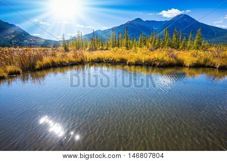 Gorgeous sunset on the Vermilion Lakes in the mountains of Banff National Park. Rocky Mountains, Canada. Concept of active tourism and ecotourism