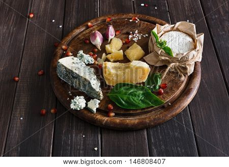 Cheese delikatessen closeup on rustic wood. Wooden round desk with blue cheese roquefort, parmesan, camembert and brie cuts decorated with garlic, pomegranate and basil, french cuisine ingredients
