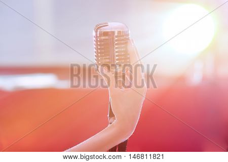 Female hand holding retro microphone, close up