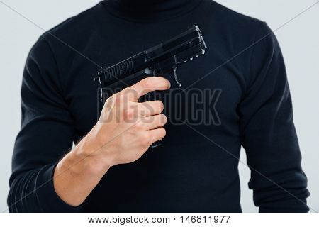 Closeup of man in black clothes standing and holding a gun
