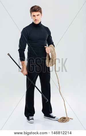 Full length of man offender with rope and crowbar