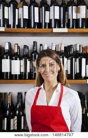 Confident Saleswoman Standing Against Shelves In Wine Shop