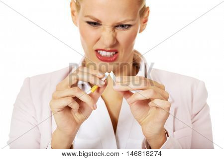 Agressive business woman breaking cigarette