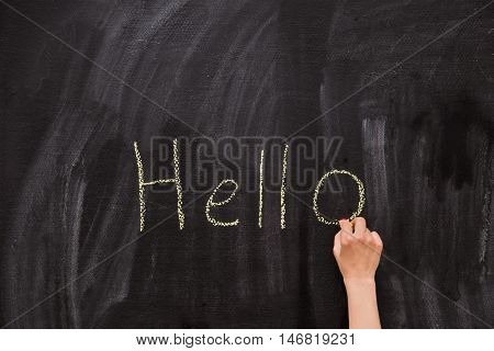 Closeup of child's hand writing Hello word with chalk on the backboard in school class. Education elementary school learning back to school concept. schoolboy writing on chalk board in classroom.