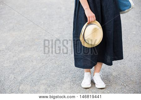 Closeup of woman's hand holding nice straw hat. Woman in long dress and white sneakers with a hat in her hand walking in the park. Summer and lifestyle concept.