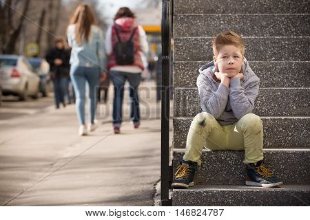 Child sitting on the stone steps. Portrait of handsome kid boy wearing casual sitting on the stairs on the street. Stylish boy looking at camera. Teenage boy child outdoors in summer or spring.