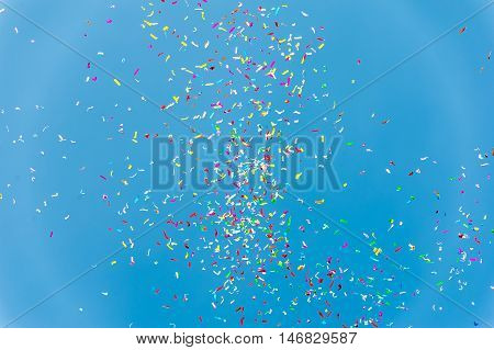 Close up of colorful confetti against a blue sky