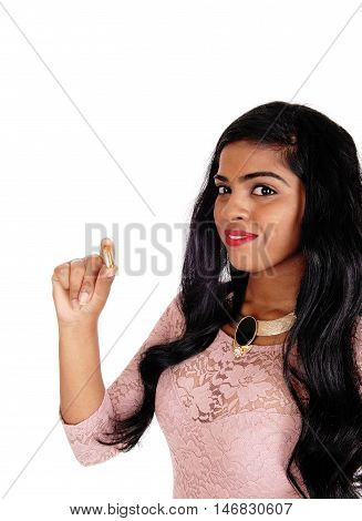 A beautiful young woman with long black hair holding a vitamin pill in her hand isolated for white background.
