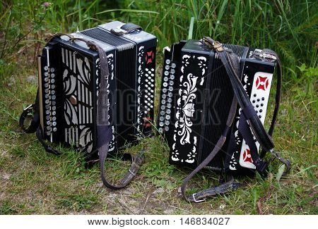 Two accordions are lying on the grass