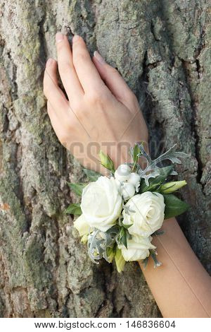 White and green wrist corsage on a hand