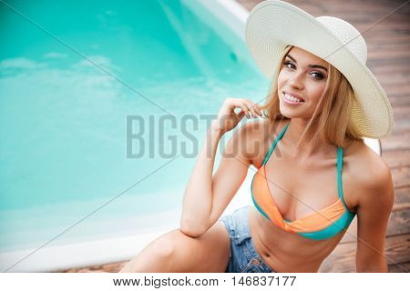 Happy cheerful young woman in hat with blonde hair sitting near swiming pool
