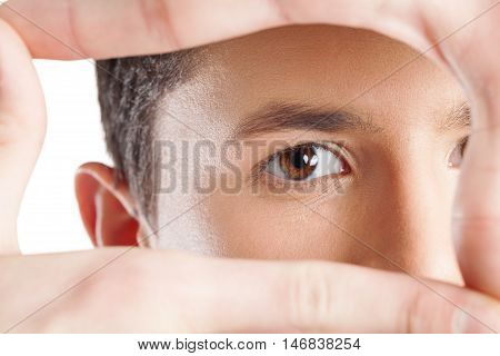 Close-up shot of young man's eye looking through frame