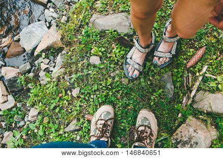 Hiking Shoes On Hiker Outdoors Walking Crossing River Creek. Woman  And Men On Hike Trekking In Natu