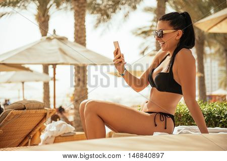 Beautiful girl surfing the net on the beach.
