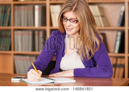 Portrait of smiling female student making notes with book shelves on background
