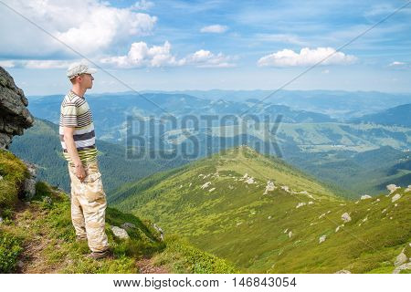 hiker looking at the horizon. Traveler on the peak in Carpathian mountains. Young man look out to view at top of rock cliff on blue cloudy sky background. Man hiker enjoying view of mountains