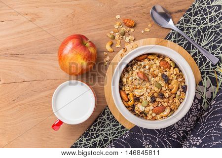 Bowl of cereal cup of milk and an apple on wooden table with spilled cereal cloth napkin and silver spoon room for text