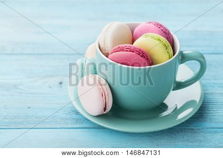 Cake macaron or macaroon in cup on turquoise background. Flavor almond cookies, pastel colors, vintage card.