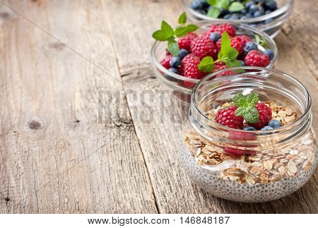 Healthy dietary breakfast. Chia pudding with muesli raspberries blueberries in a glass bowl fresh berries on old wooden background