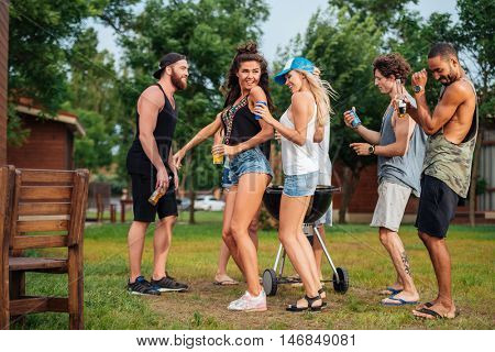 Group of happy young friends dacing and having fun outdoors