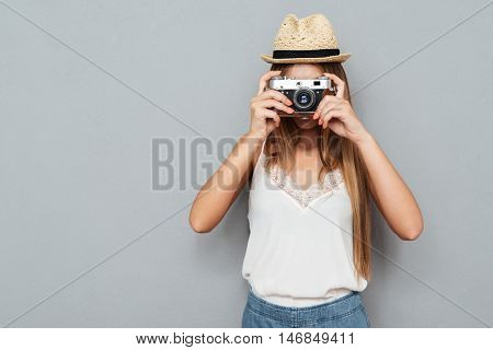 Young blonde woman in hat making photo with camera isolated on a gray background