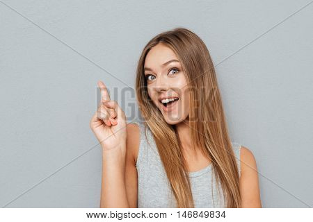 Young happy woman poiting finger up at copyspace isolated on a gray background