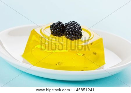 Pineapple jelly pudding decorated blackberries on a white plate on a blue background.
