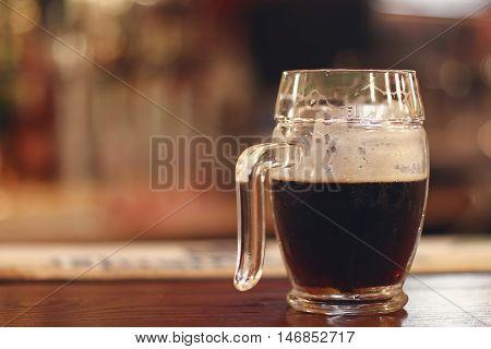 Black beer on wooden table. Half mug Black beer.