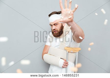 Unhappy irritated bandaged bearded man catching tablets with hand over gray background