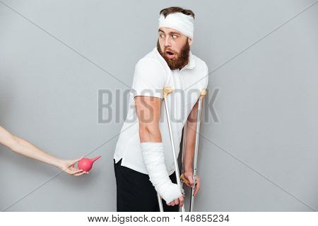 Frightful panicked injured man going to have an enema procedure over gray background