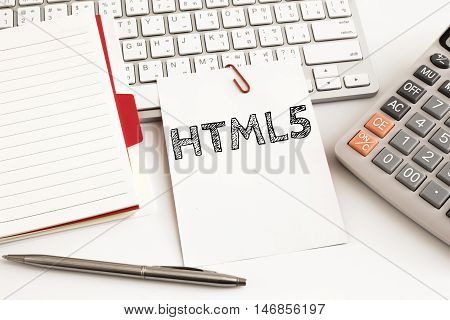 Word text HTML 5 on white paper card on office table / business concept