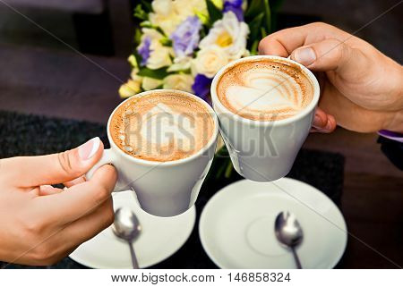 Man and woman's hands and coffee cups with hearts