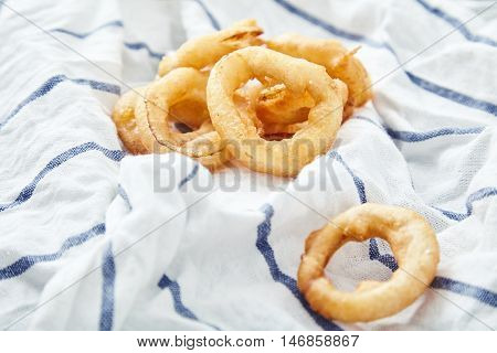 Close up shot of delicious, crunchy, golden onion rings on kitchen towel. Appetizing flavorful snack for beer. Fastfood from the deep fryer.